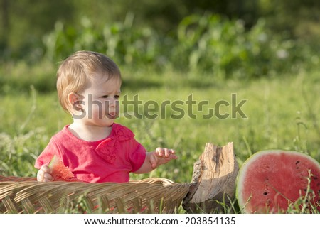 Cute little baby in basket playing with  - stock photo