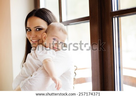 Cute little baby in the arms of her mother in a living room. - stock photo