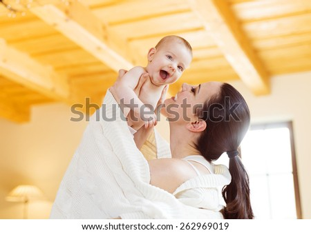 Cute little baby in the arms of her mother in their living room. - stock photo