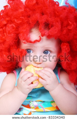 cute little baby in the bright red wig with an apple in his hands