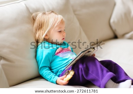 Cute little baby or toddler girl reading a book on a leather couch indoors on a rainy day - stock photo