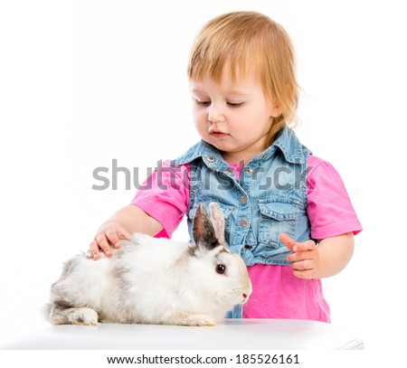 cute little baby petting Easter bunny on a white background - stock photo