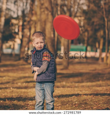 cute little baby  playing frisbee, outdoor portrait. Toned image - stock photo