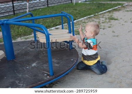 cute little baby playing on the playground outdoor - stock photo