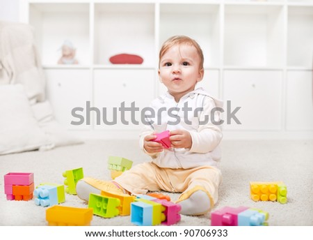Cute little baby playing with colorful blocks