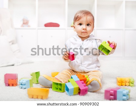 Cute little baby playing with colorful blocks - stock photo