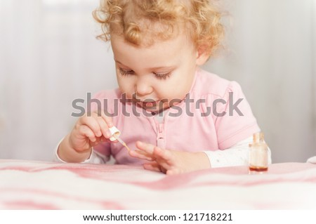 Cute little baby playing with mothers manicure cosmetics - stock photo