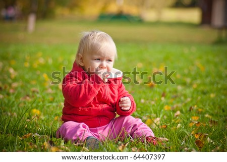 cute little baby sit on green grass with yellow leafs in park
