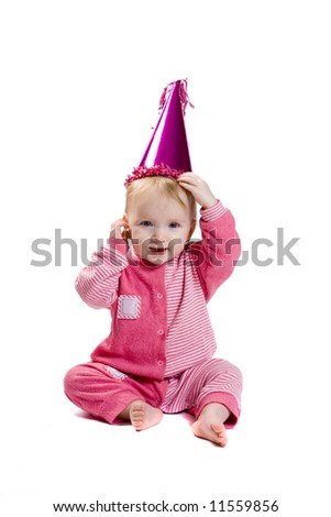 Cute little baby sitting in clown fancy dress and pink cap, with hands on his head, isolated on white