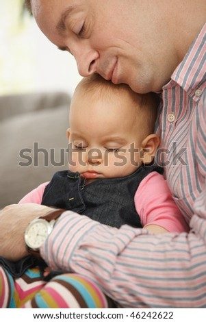 Cute little baby sleeping held in father's arm at home. - stock photo