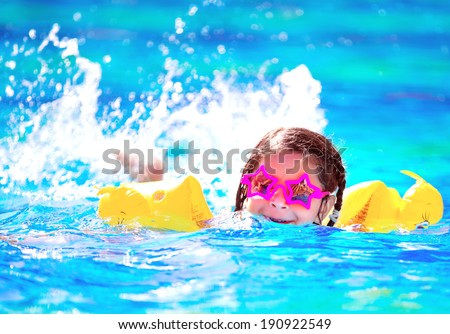 Cute little baby swimming in the pool, wearing funny sunglasses, enjoying summer weekend in aqua park, holidays and vacation concept - stock photo