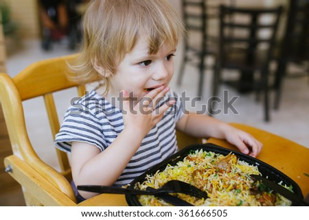 Cute little baby toddler girl having her lunch rice sitting in a wooden baby chair