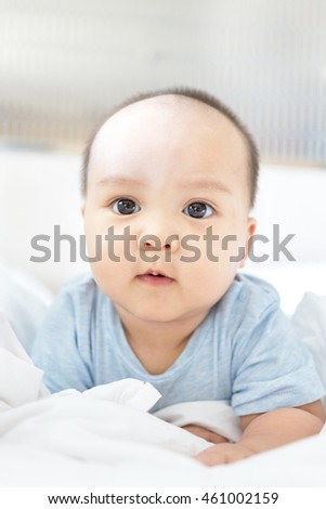 cute little baby with big lovely eyes on bed