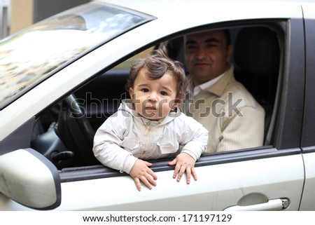 cute little baby with his father in the car - stock photo