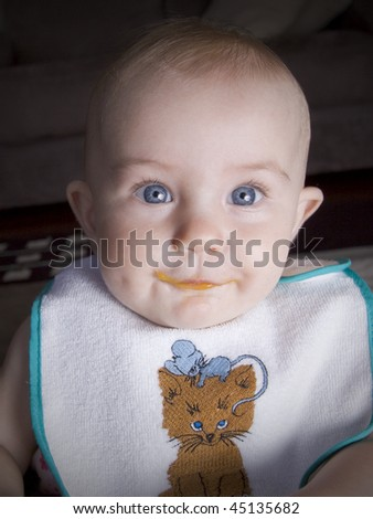 Cute little baby with some left over food all over her mouth - stock photo