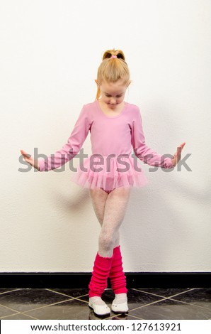 Cute little ballerina dancing against white wall. - stock photo