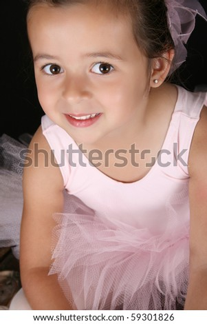 Cute little ballet girl wearing a tutu looking up at the camera - stock photo