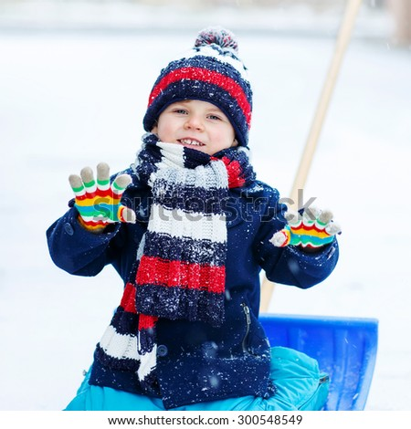 Cute little beautiful kid boy in colorful winter clothes sitting on snow shovel, outdoors during snowfall on cold day. Active outdoors leisure with children in winter. - stock photo