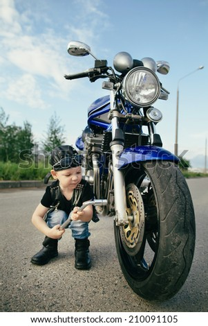 cute little biker repairs motorcycle on road  - stock photo