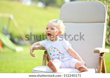 Cute little blond baby girl with flower in her hair sitting on a wooden teak chair in a garden, she is laughing and enjoying the sun - stock photo