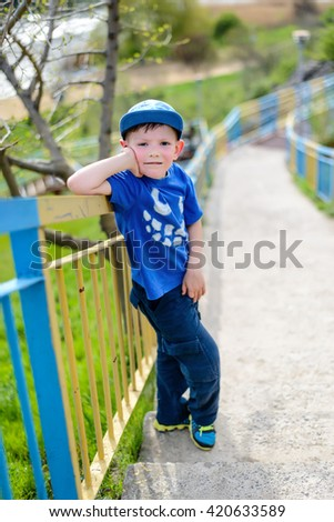 Cute little blond boy in blue hat, shirt and pants leaning on railing at hill outside during summer - stock photo