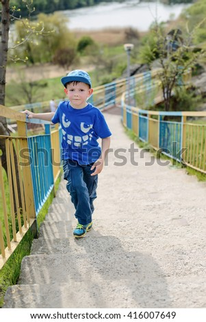 Cute little blond boy in blue hat, shirt and pants leaning on railing with folded arms at hill outside during summer - stock photo