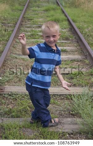 Cute little blond boy playing on railway - stock photo