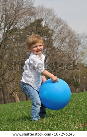 cute little blond boy playing outside with a big blue ball - stock photo