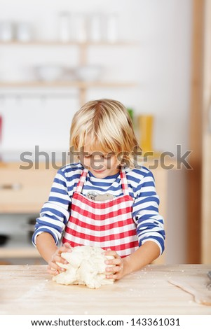 Cute little blond girl baking cookies standing at the kitchen counter knead pastry or dough - stock photo