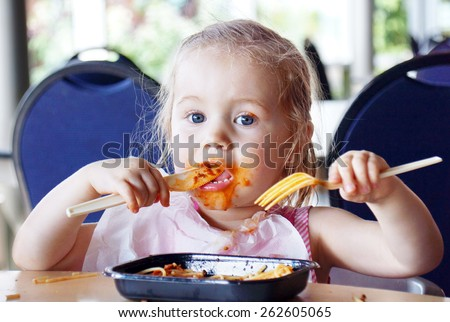 Cute little blond girl eating spaghetti pasta making a mess - stock photo