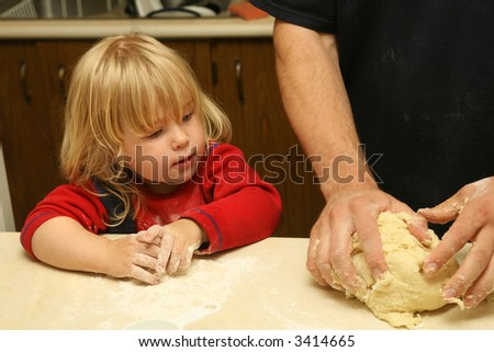 cute little blond girl helping dad knead the dough in the kitchen - stock photo