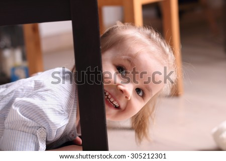 Cute little blond girl laughing peeking out from behind table leg - stock photo