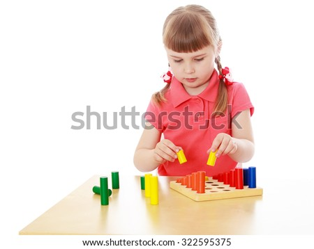 Cute little blond girl with short bangs and short pigtails on her head sitting at a table in a Montessori kindergarten . the girl is working with Montessori material-Isolated on white background - stock photo