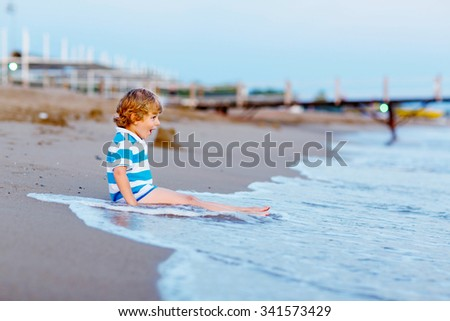 cute little blond kid boy having fun with building sand castle on the beach of ocean or see by sunset. Happy child spending active vacations. - stock photo