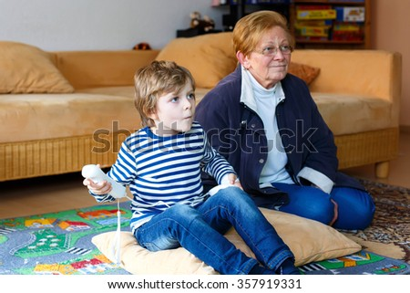 Cute little blond kid boy playing with a video game console with his grandmother. Family of two having fun together at home. - stock photo