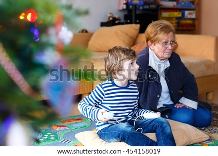 Cute little blond kid boy playing with a video game console with his grandmother on Christmas. Family of two having fun together at home. - stock photo