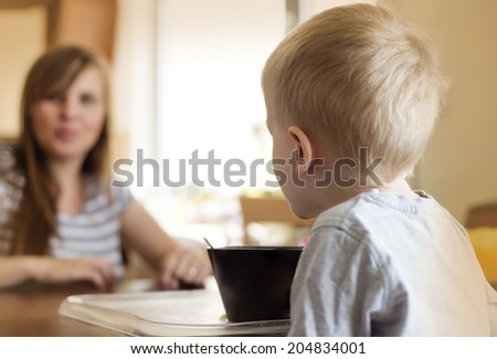 Cute little blonde boy eating breakfast with his mother in the kitchen