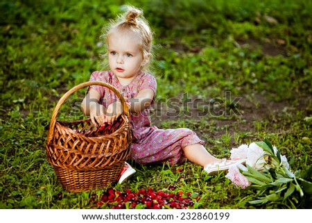 Cute little blonde girl in a pink jumpsuit eating raspberries from the basket - stock photo