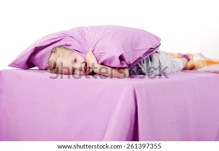Cute little blonde girl laughing in bed - stock photo