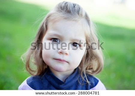 Cute little blonde girl looking at camera with grass of background - stock photo