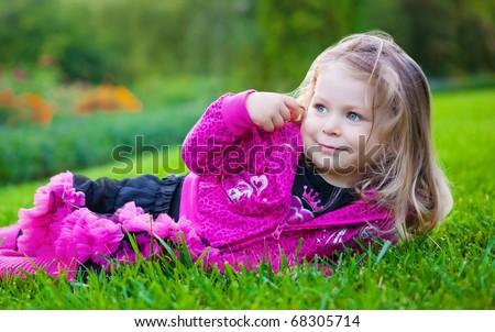 Cute little blonde girl lying on a green grass - stock photo