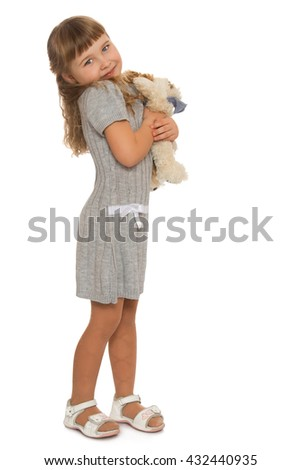 Cute little blonde girl pressed to his chest a stuffed toy - Isolated on white background - stock photo