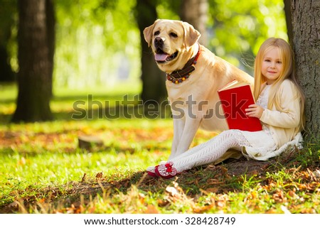 Cute little blonde girl sitting with dog on the grass in the forest - stock photo