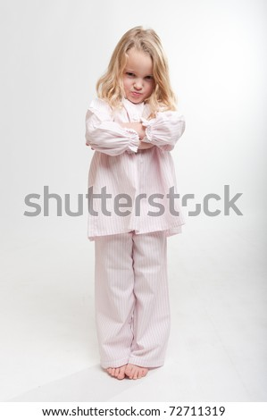 Cute little blonde girl with an angry expression in her pajamas - stock photo