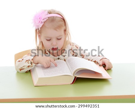 Cute little blonde girl with rim in the form of a bow on his head sitting at a table and reading a book, the girl runs her finger across the letters she is studying grammar-Isolated on white - stock photo