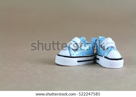 Cute little blue baby shoe on wood background