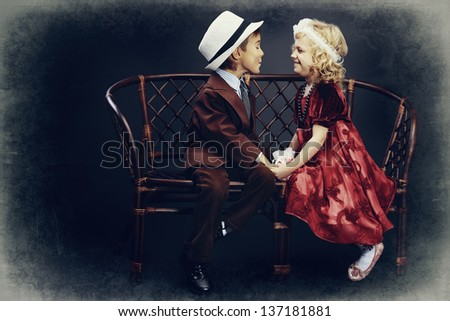 Cute little boy admitted in love the charming little lady. Retro style. - stock photo