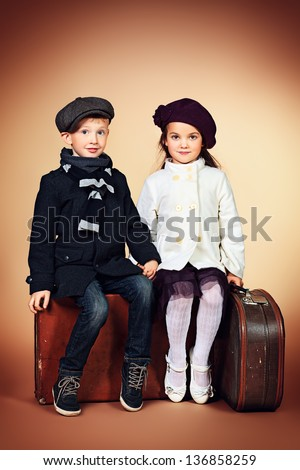 Cute little boy and girl are sitting on their old suitcases. Retro style. - stock photo