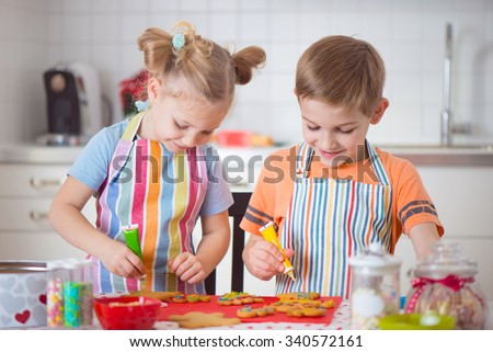 Cute little boy and girl preparing Christmas cookies at home - stock photo