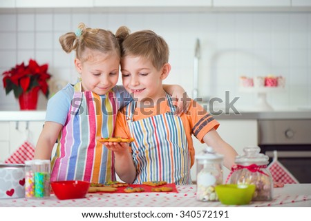 Cute little boy and girl preparing Christmas cookies at home